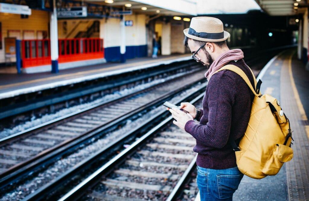 Człowiek ze smartfonem na stacji kolejowej